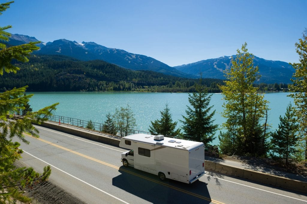 RV driving along a spectacular section of Highway 99 past Green Lake in Whistler, BC