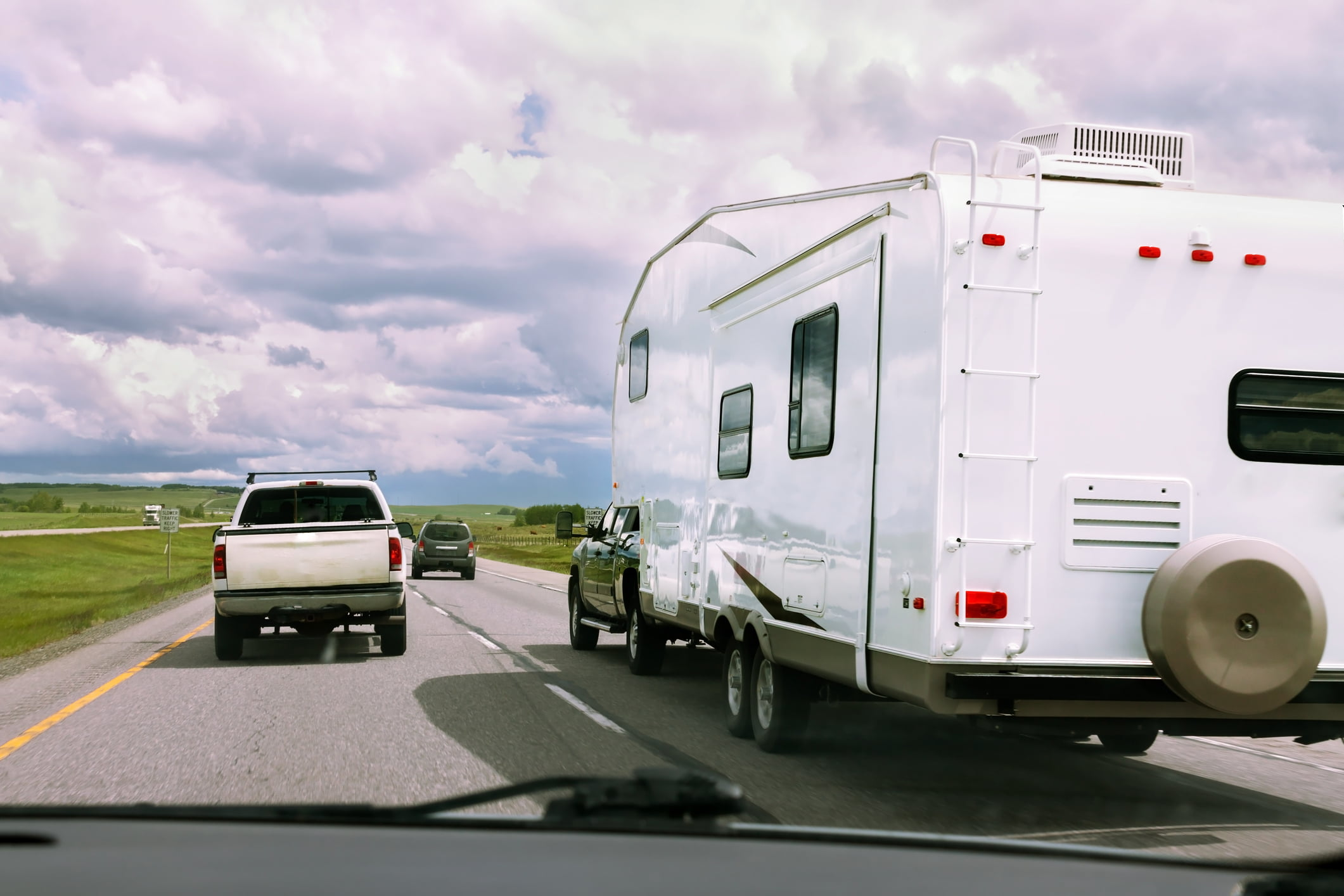 RV being pulled by truck and other vehicles on road with cloudy skies on sunny day.