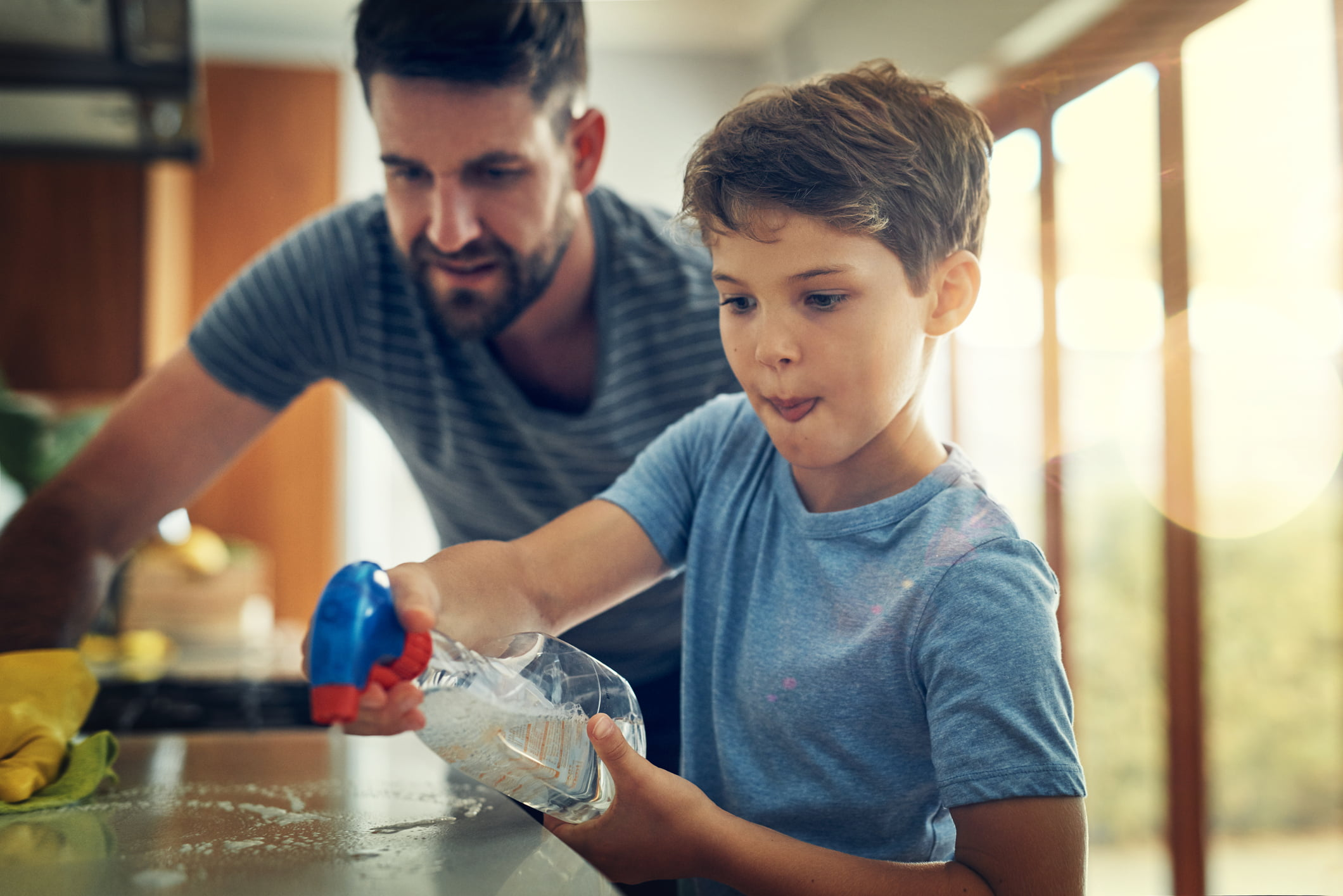 Shot of a father and son cleaning the kitchen counter together at home