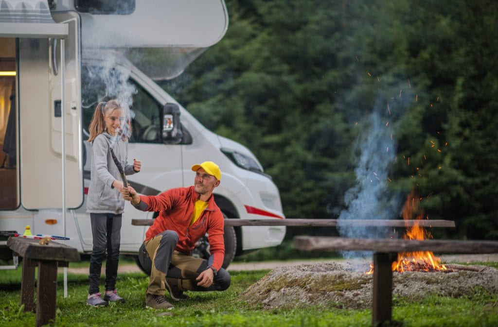 Summer Family RV Camp. Father Having Fun with His Daughter in Front of Campfire. RV Class B Motorhome in a Background.