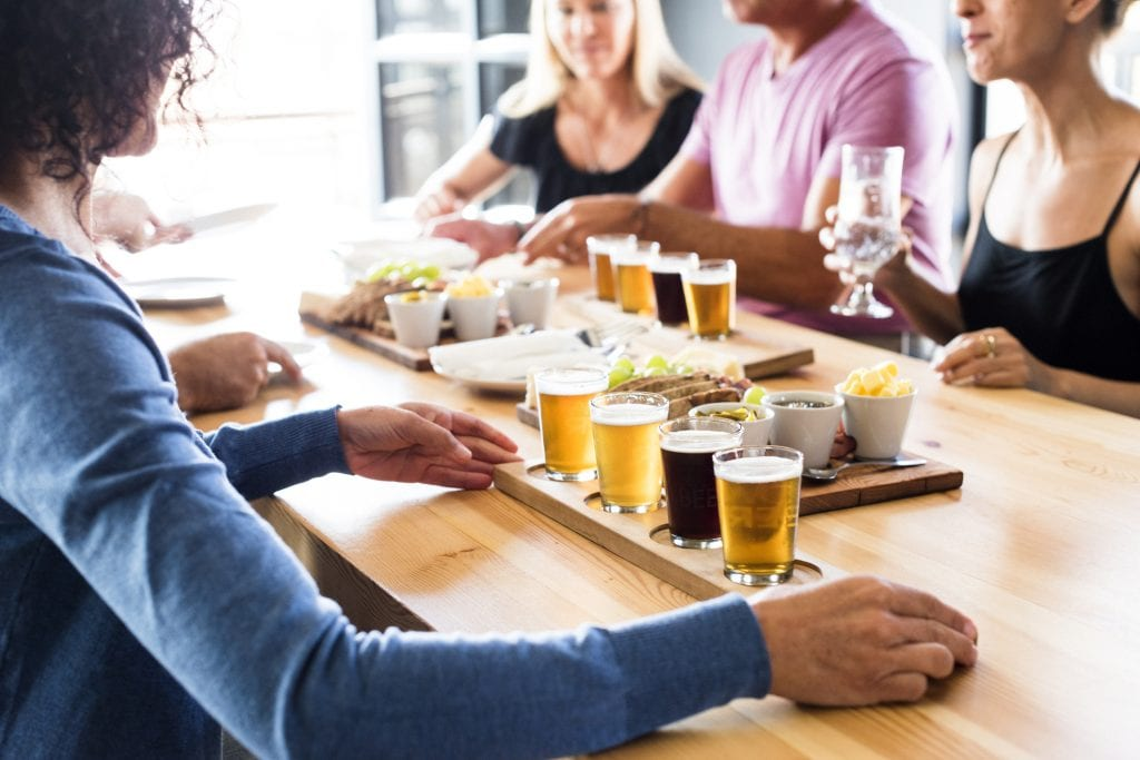 Group of friends seated at a table inside a brewery at daytime enjoying lunch & craft beer tasting together.
