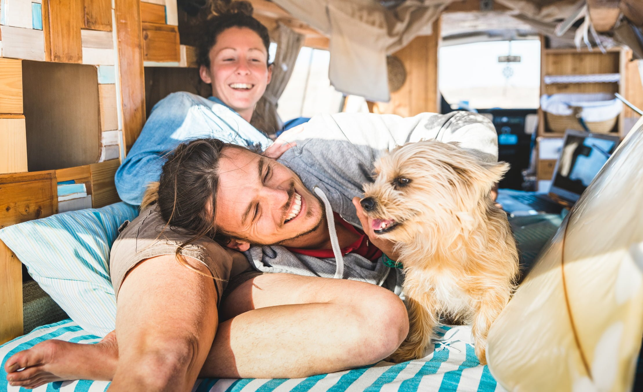 Hippie couple with funny dog traveling together on vintage minivan transport - Life inspiration concept with indie people on mini van adventure trip in relax moment - Bright warm retro filter