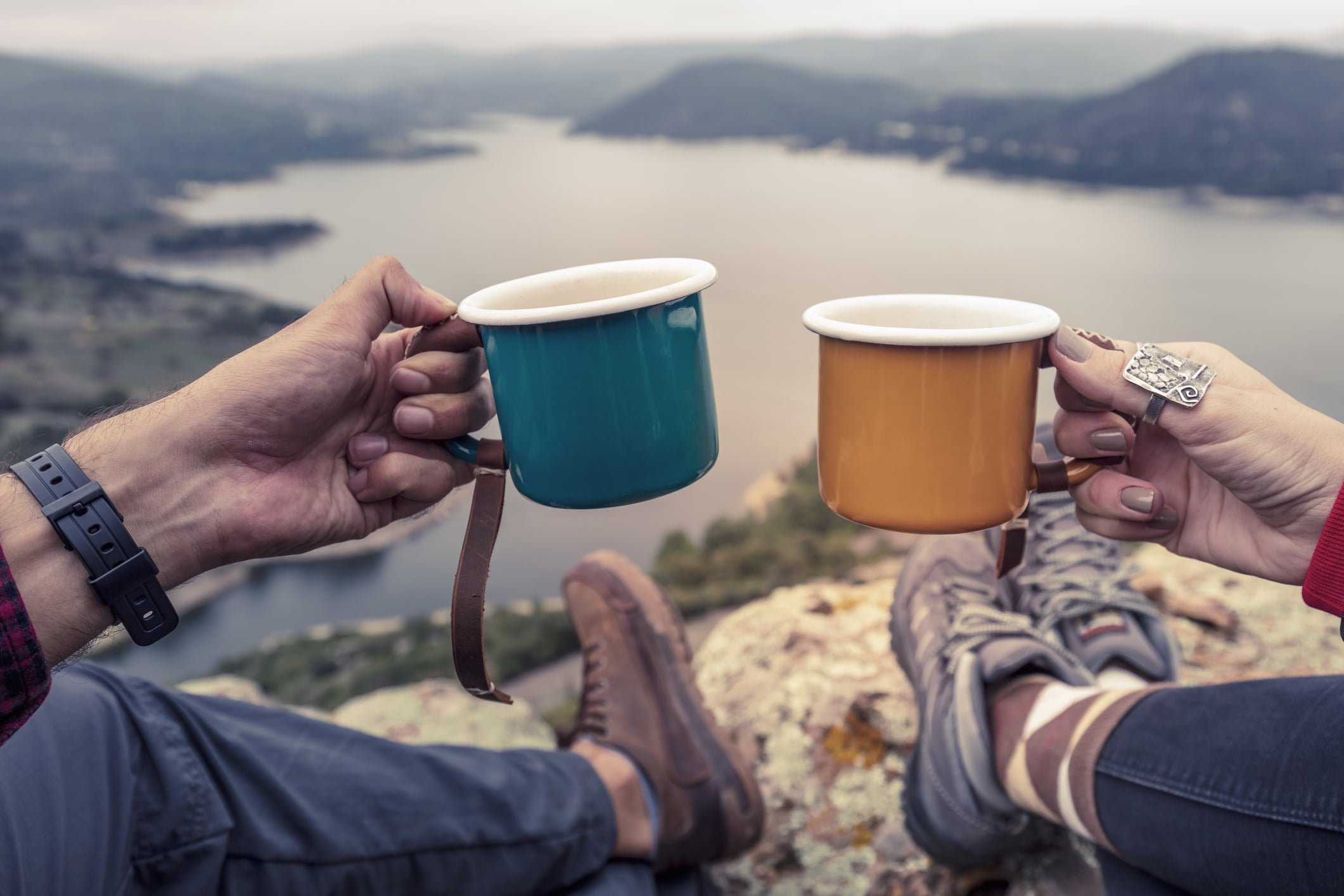 camper couple holding enamel cups at peak