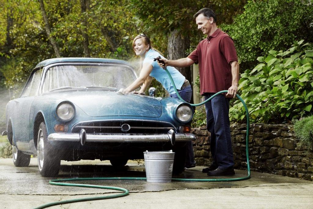 Couple Washing Vintage Car