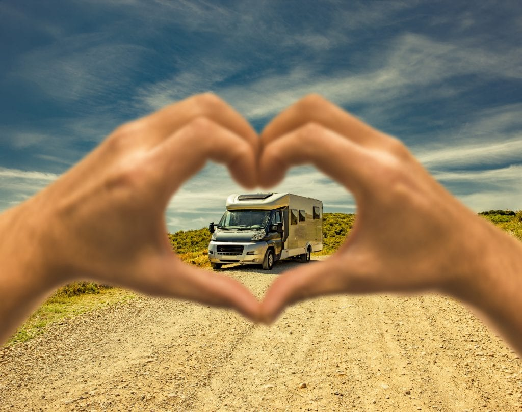 Motorhome on a dust road with a heart shaped human hand