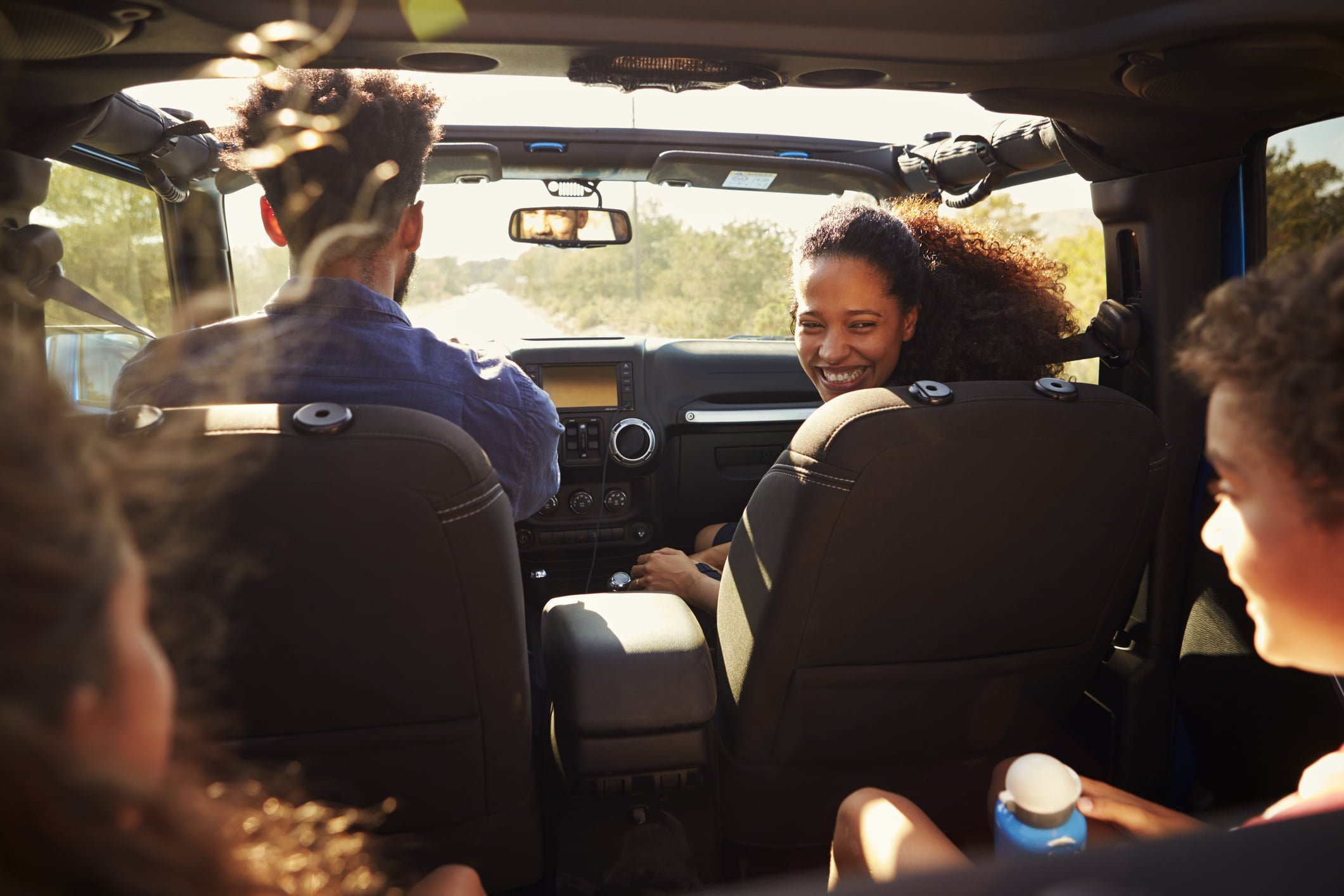 Excited family on a road trip in car, rear passenger