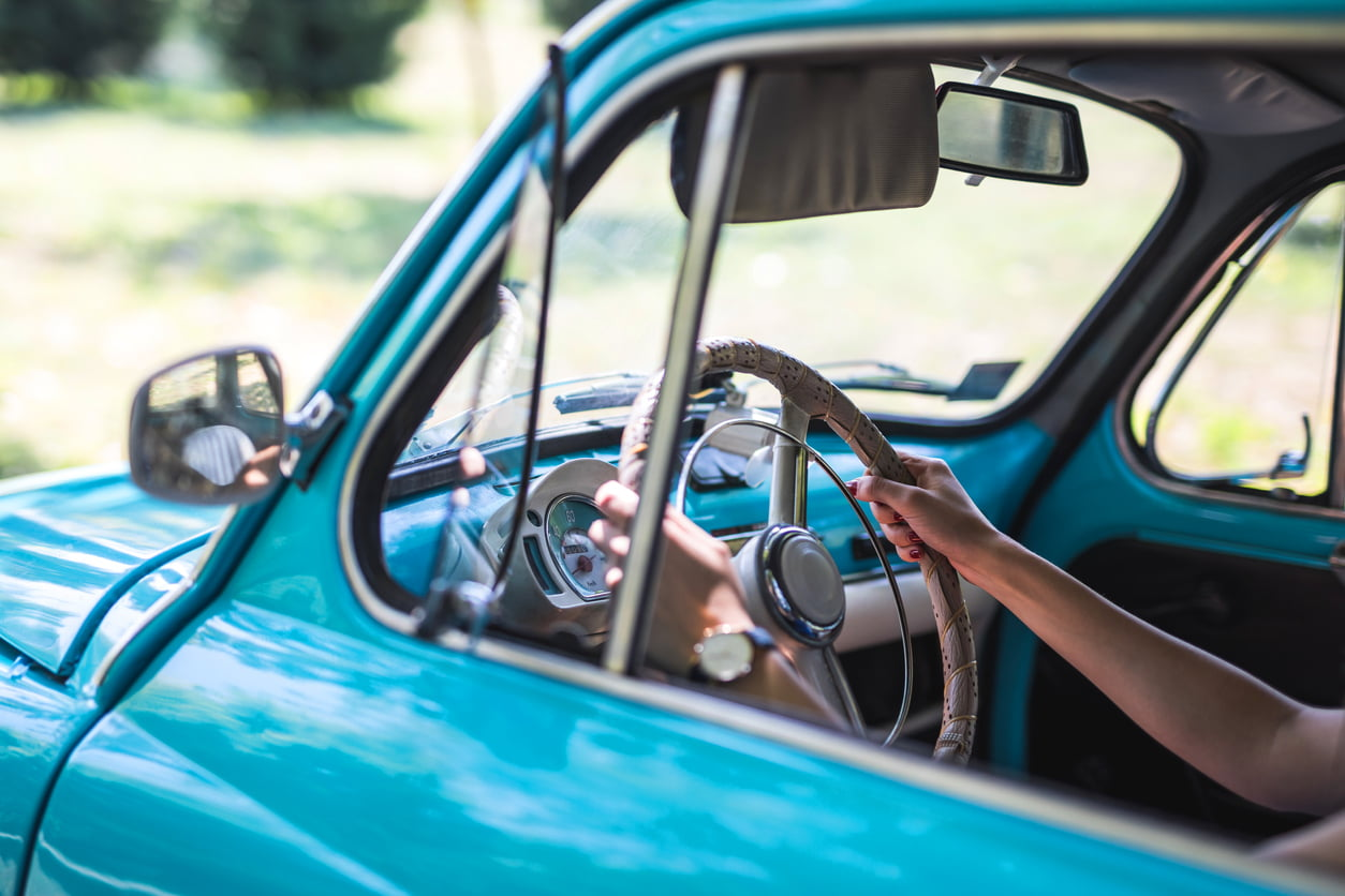 Woman`s hands on steering wheel of vintage car