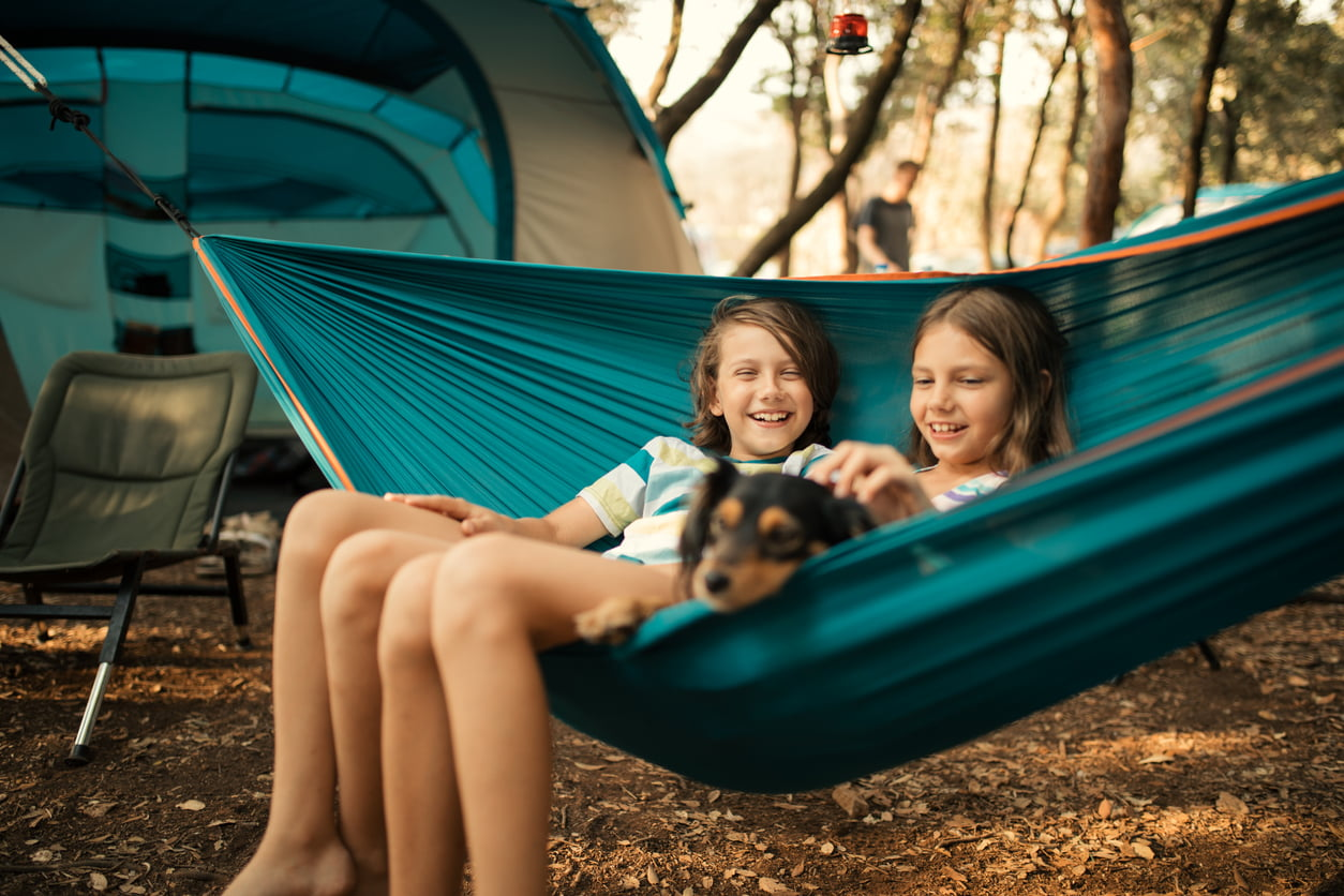 Children relaxing in hammock with dog