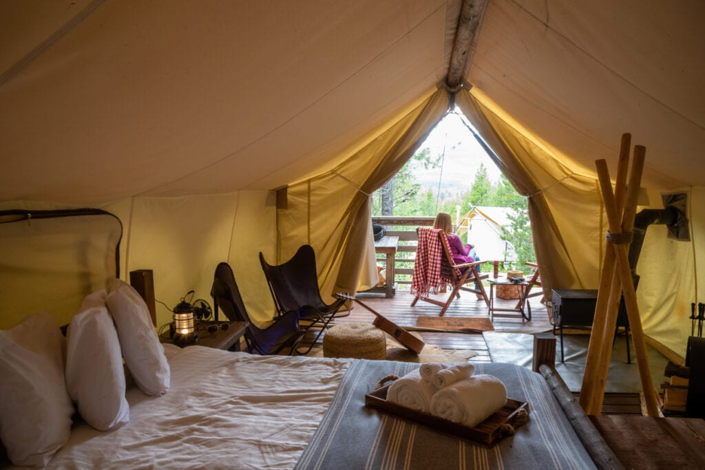 Woman sitting outside luxury tent on glamping trip in Glacier National Park