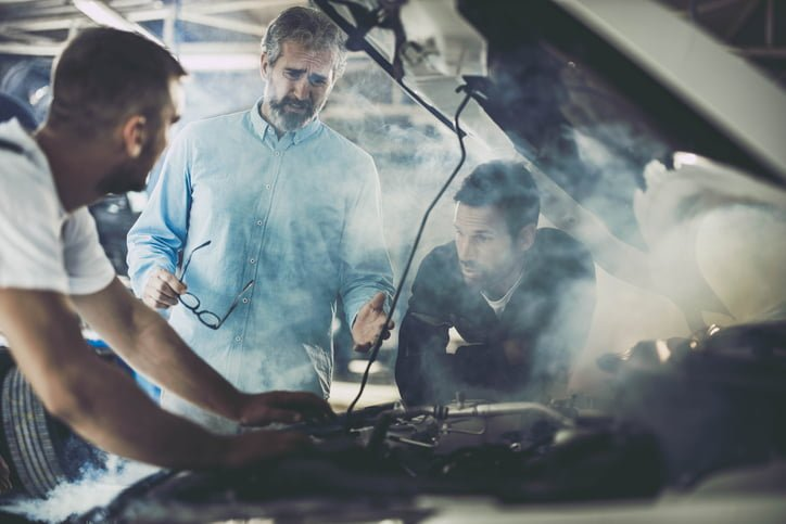 Mid adult customer and mechanics feeling frustrated while the car is smoking in a repair shop.