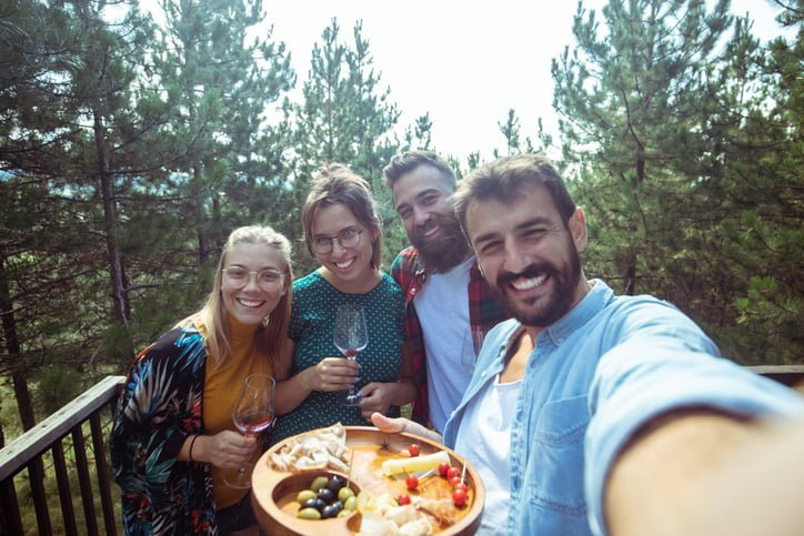 View of four friends taking a selfie cheerfully smiling at the camera. Snacks they're enjoying are also visible in the picture.