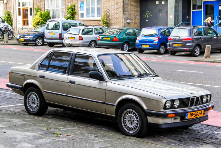 BMW E30 3-series is parked in the city street.