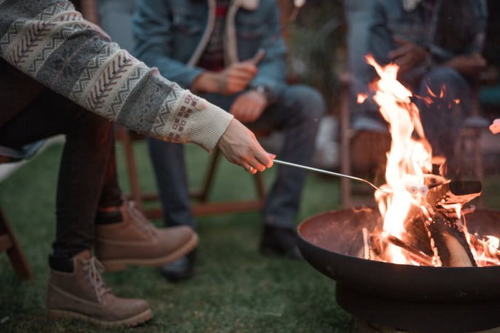 Friends roasting marshmallows on portable fireplace