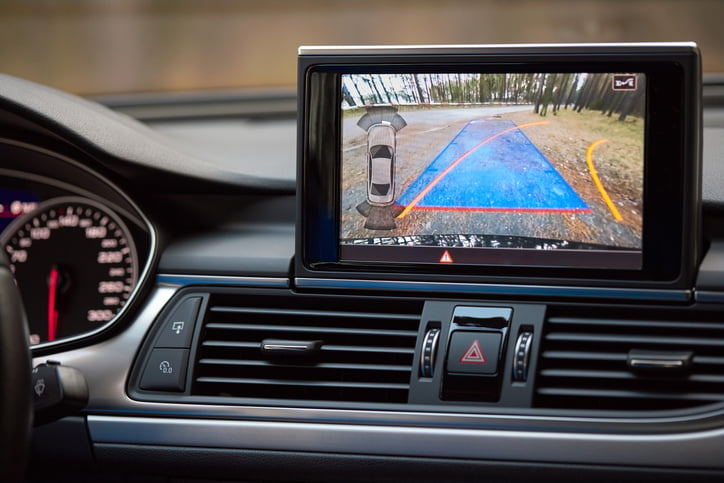 Interior of premium car with rearview camera dynamic trajectory turning lines and parking assistant steering wheel turned right. Driver assistance parking system. Help assist options of luxury car.