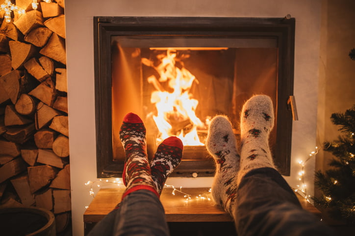 Human legs in socks in front of a cottage fireplace during the off season.