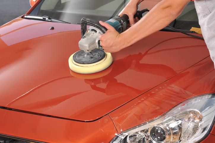 Worker waxing orange car by polishing machine