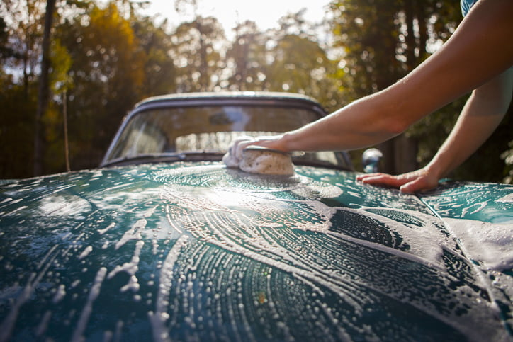 Hand washing a collector car with a sponge