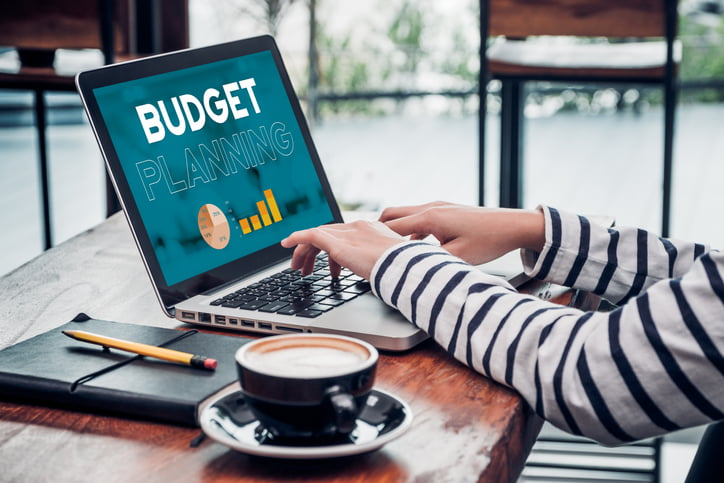 Close up hands budget planning for online media advertising at cafe restaurant.