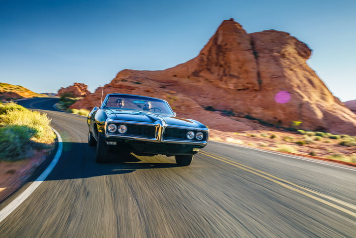 Couple driving together in a classic car through desert at high speed.